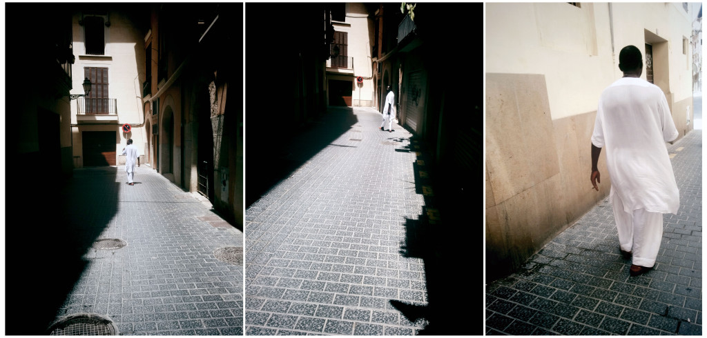 A triptych image. The first two images show a black man wearing a long white flowing shirt and loose white trousers walking down a street which is in shadow. The third image shows the same man walking on a bright street. He is holding a cigarette in his left hand.
