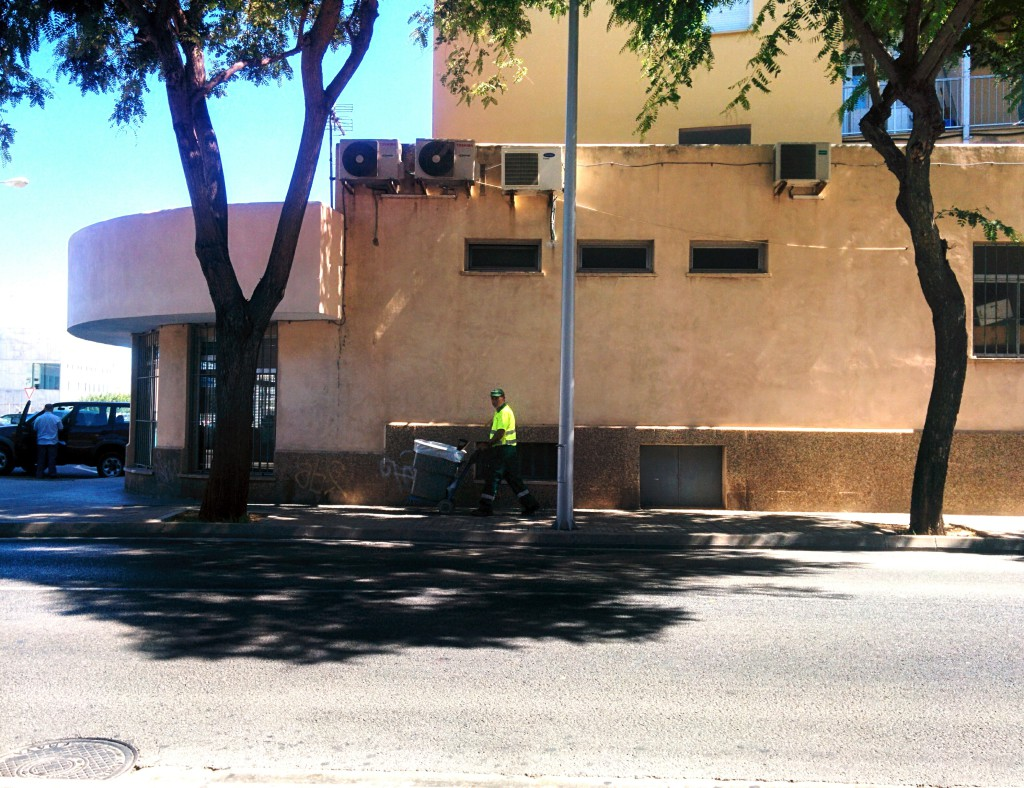 A picture of a street cleaner walking along a street, in the shadow of a building on a mid morning very hot day, in Palma de Mallorca pushing his cart.