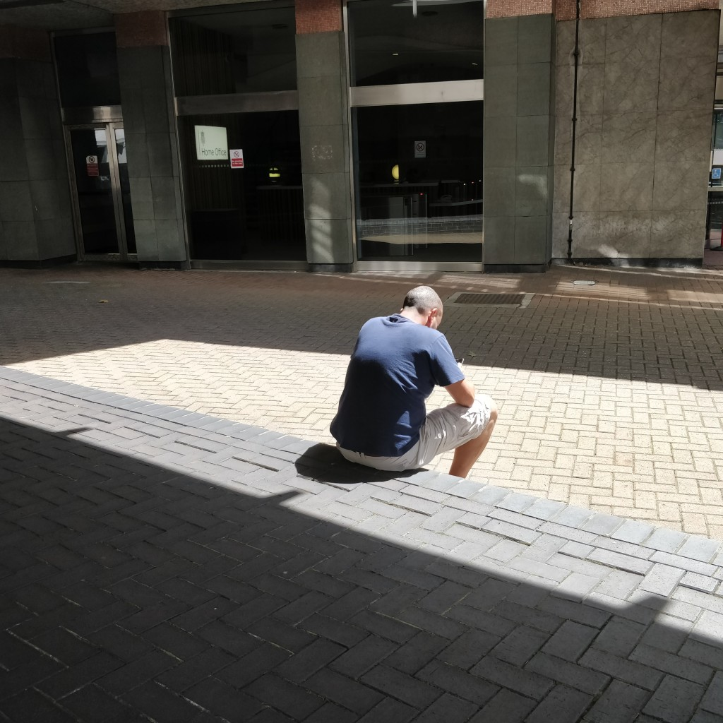 Man sitting on concrete step looking down. There are shadows all around him.