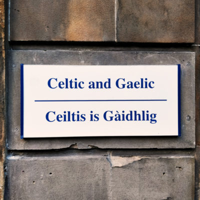 """A sign saying """"Celtic and Irish"""", in both English and Scots Gaelic on a building of the University of Glasgow, Glasgow Scotland"""